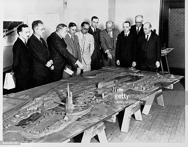 A group of architects and amusement consultants examine a model of the fairgrounds for the 1933 World's Fair in Chicago Illinois USA