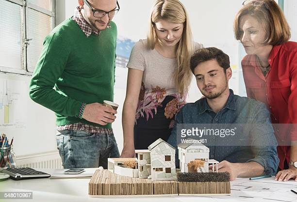 Group of architects in office with architectural model