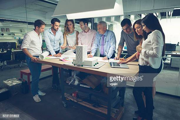 Group of architects reviewing architectural model in the office.