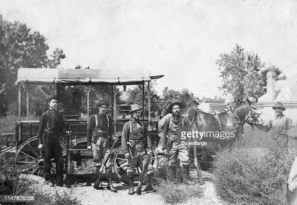 Group Of Armed Men A Group Of Four Men Standing In Front Of MudWagon They All Have Rifles Revolvers One Of The Men Has A Fancy Hand Carved Steer...