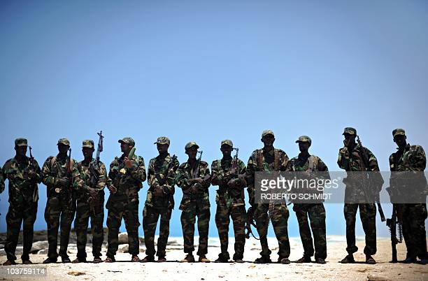 A group of armed militiamen wearing uniforms line up on a beach in Hobyo on August 20 2010 Hobyo has no schools no clinics and bad drinking water...