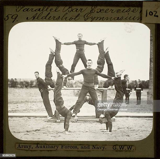 A group of Army Auxiliary Forces and Navy members perform gymnastic exercises on parallel bars at the Aldershot Gymnasium Great Britain ca1880s