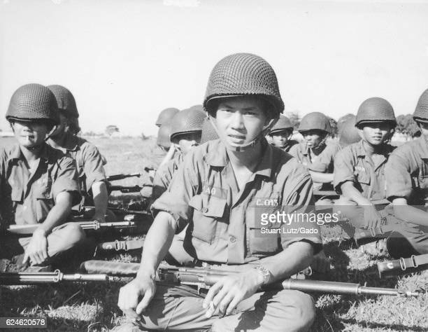 A group of Army of the Republic of Vietnam soldiers seated on the ground with their rifles laid across their laps Vietnam 1968