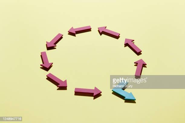 a group of arrows arranged in a circle with one leaving - richard drury stock pictures, royalty-free photos & images