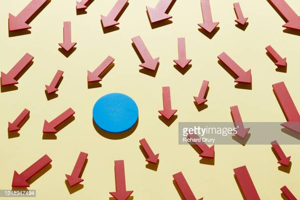 a group of arrows moving down around a blue circle - richard drury stock pictures, royalty-free photos & images