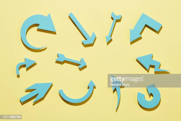 a group of arrows pointing at the same spot - coloured background stock pictures, royalty-free photos & images