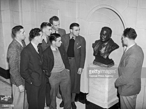 A group of Arsenal players admire a bronze memorial bust of the late club manager Herbert Chapman by Jacob Epstein on display at the Arsenal Stadium...