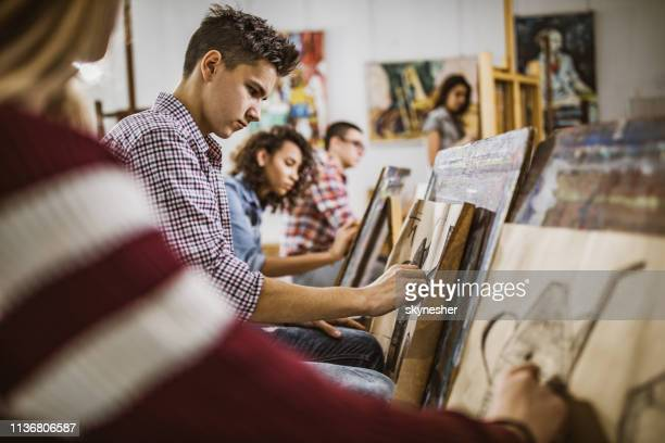 group of art students drawing paintings at art studio. - adolescence stock pictures, royalty-free photos & images