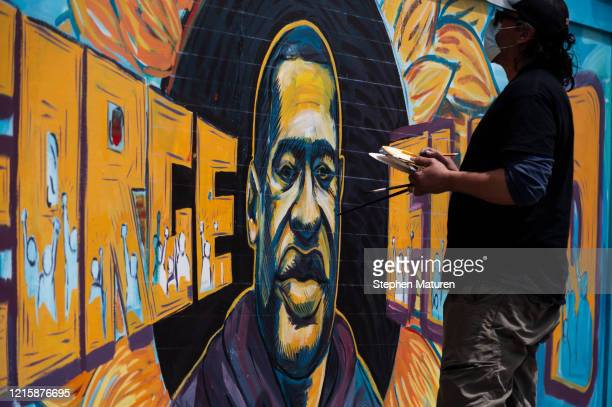 Group of artists paint a mural of George Floyd on the wall outside of Cup Foods, where Floyd was killed in police custody, on May 28, 2020 in...