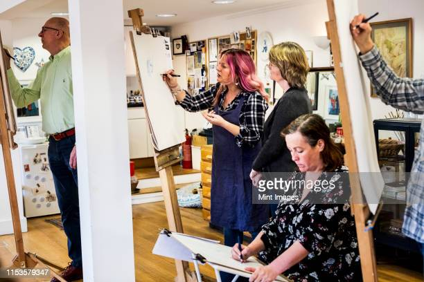 group of artists standing and sitting at easels, drawing. - art stock pictures, royalty-free photos & images