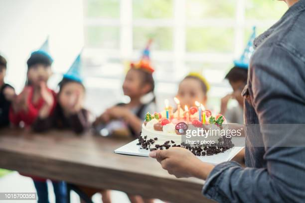 group of asian adorable kids looking at birthday cake with candle. - birthday party stock pictures, royalty-free photos & images