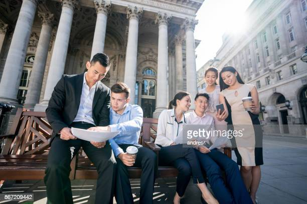 Group of Asian business people working outdoors looking at some documents