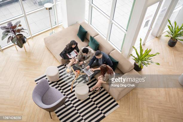 group of asian chinese white collar worker sitting on sofa having discussion in the office - east asian ethnicity stock pictures, royalty-free photos & images