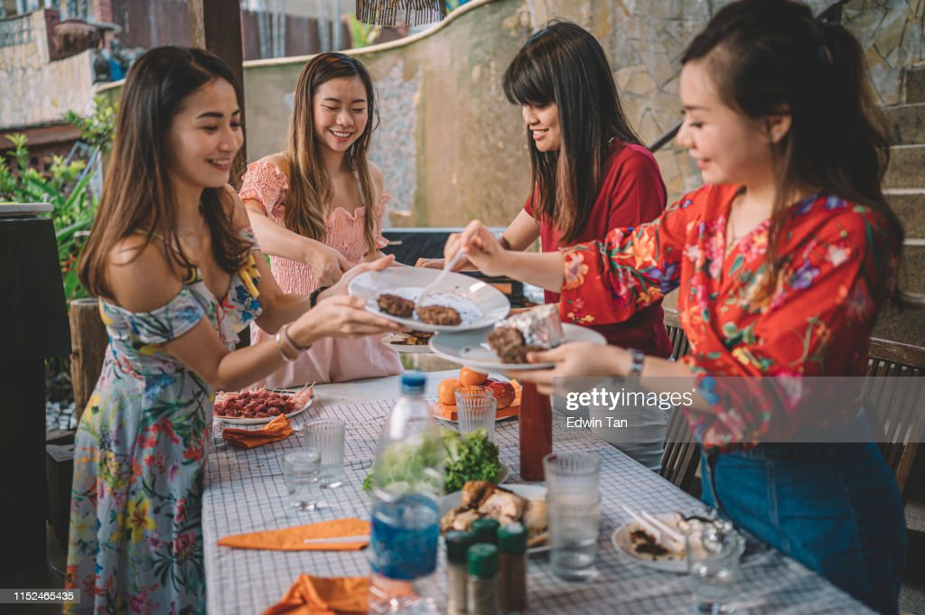 A group of Asian multi ethic female cleaning up dishes after party : Stock Photo