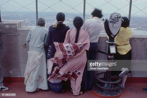 A group of Asian people looking out over Manhattan from the 86th floor observation deck of the Empire State Building New York City 1985