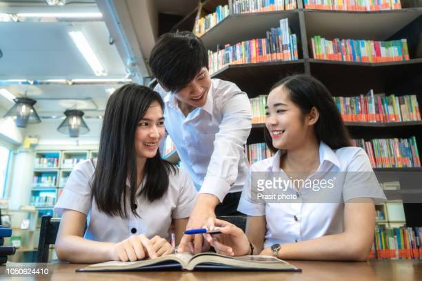 Group of Asian students studying together in library at university.