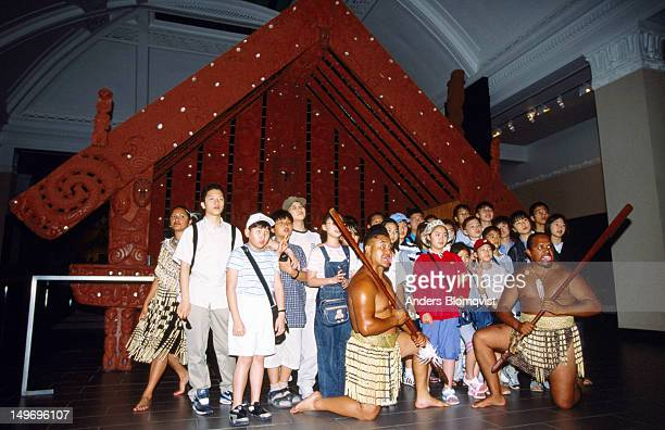 Group of Asian tourists and Maori performers at War Memorial Museum.