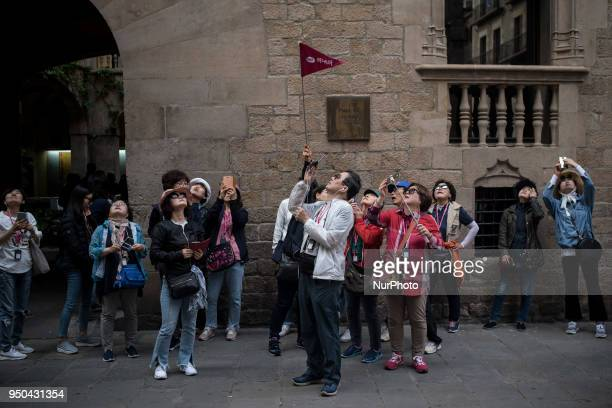 A group of Asian tourists contemplate and take photos of the Cathedral in the Gothic Quarter of Barcelona Catalonia Spain on 23 April 2018 The number...