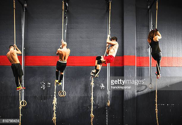 group of athlete climbing the rope on a gym - crossfit stock pictures, royalty-free photos & images