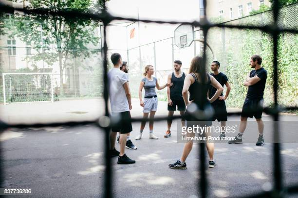 Group Of Athletes Deciding On Teams Before Friendly Basketball Game Outdoors