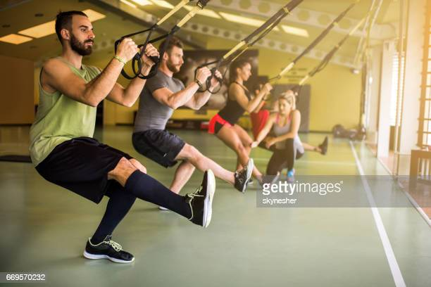 Group of athletes doing strength exercises on suspension training in a health club.
