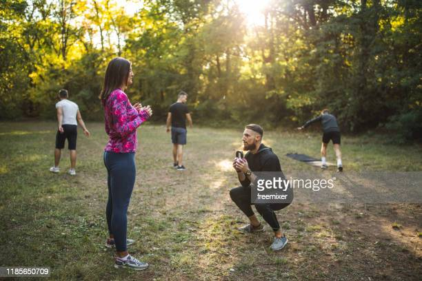 group of athletes exercising outdoors - sports training stock pictures, royalty-free photos & images
