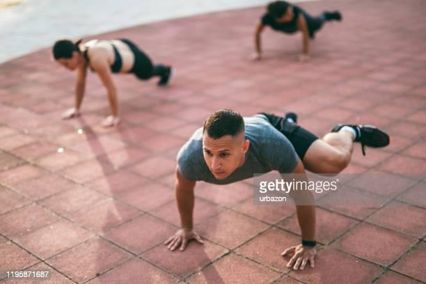 屋外で運動するアスリートのグループ - 自重トレーニング ストックフォトと画像