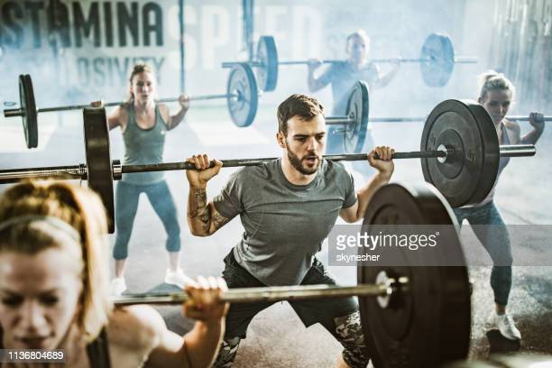 group of athletes exercising strength with barbells on cross training in a gym. - snatch weightlifting stock photos and pictures