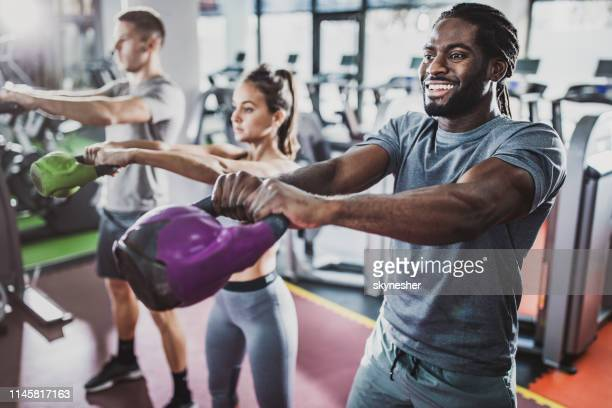 group of athletes exercising with kettle bells on cross training in a gym. - hand weight stock pictures, royalty-free photos & images