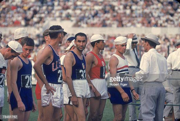 A group of athletes gather on the track before a foot race probably a long distance running event as officials look on at the 17th Summer Olympic...