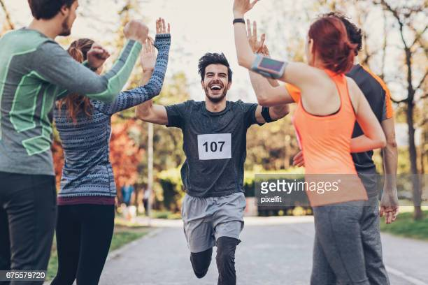 group of athletes greeting the winner at the finsh line - sports team stock pictures, royalty-free photos & images