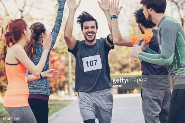 gruppe von athleten, die begrüßung des gewinners - erster platz stock-fotos und bilder
