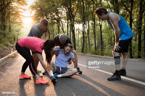 Group of athletes helping injured man during marathon race.