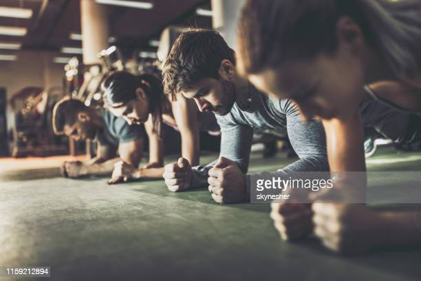 group of athletes in a plank position at health club. - plank exercise stock pictures, royalty-free photos & images