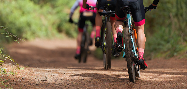 Group of athletes mountain biking on forest trail 1133672137