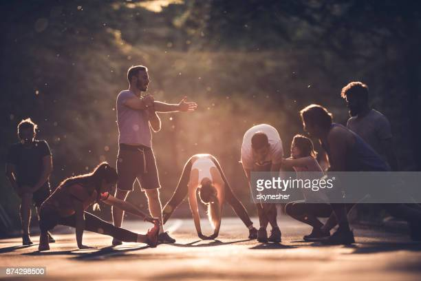 Group of athletes preparing for marathon race while warming up on the road at sunset.