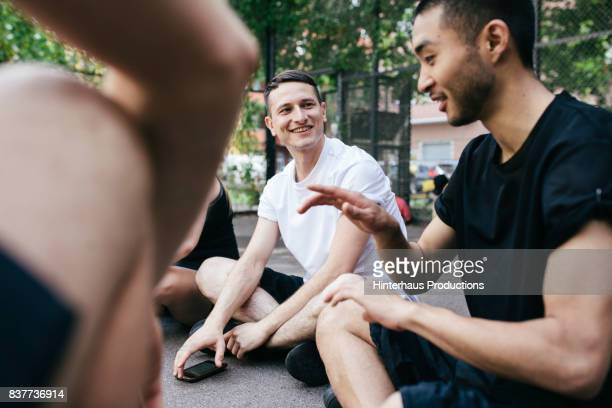 Group Of Athletes Sitting Down Discussing Basketball Before Friendly Outdoor Match