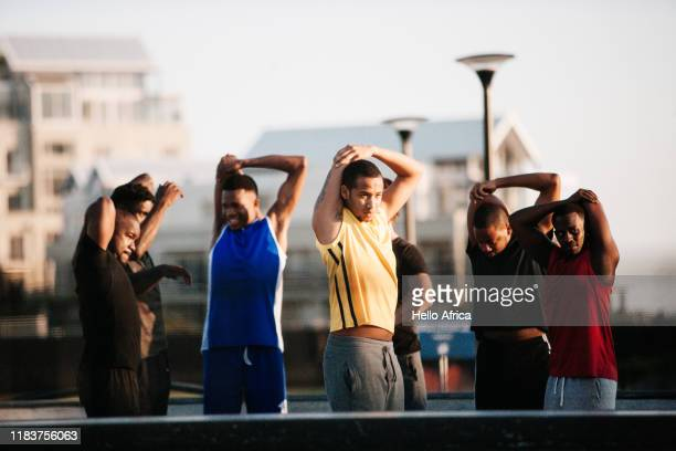 Group of athletes stretching flanks and arms