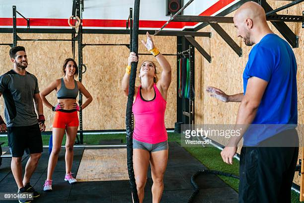 Group of athletes watching woman climbing a rope in gym