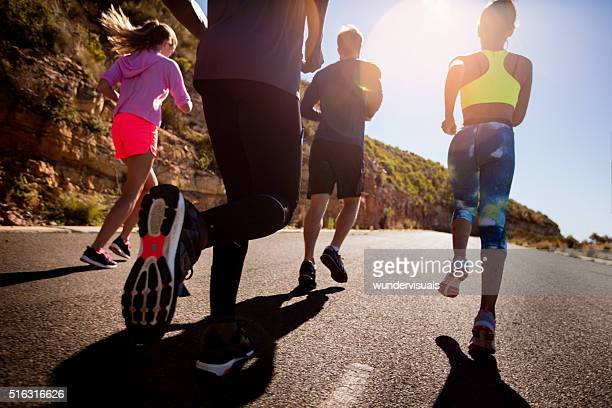 Group of athletic friends running outdoors