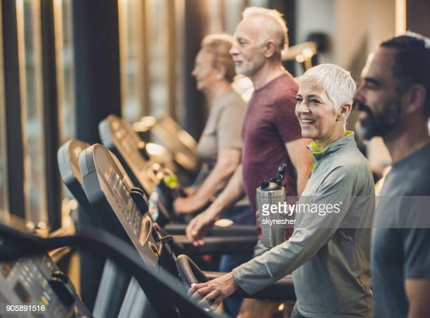 Group of athletic mature people practicing on treadmills in a gym.