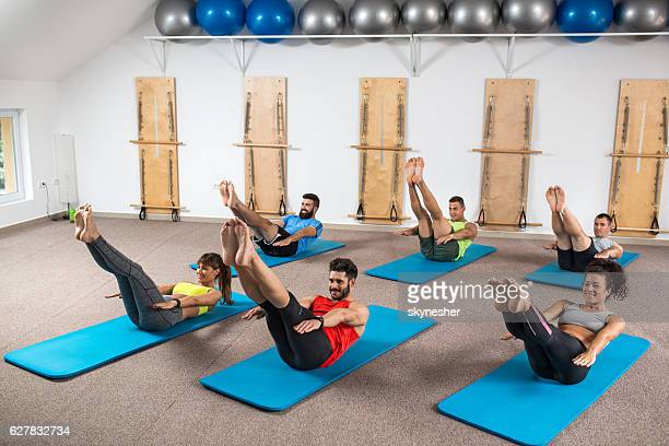 Group of athletic people exercising on Pilates training class.