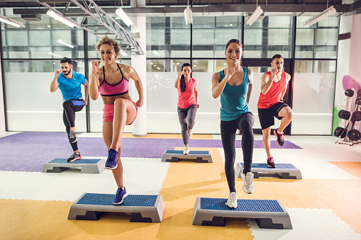 Group of athletic people exercising step aerobics in a gym. 517963642