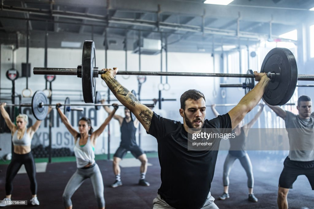 Group of athletic people exercising with barbells during cross training in a gym. : Stock Photo