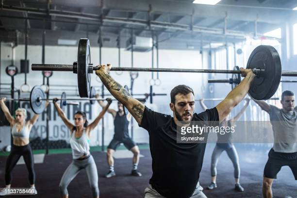 group of athletic people exercising with barbells during cross training in a gym. - snatch weightlifting stock photos and pictures