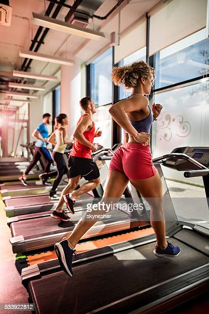 Group of athletic people jogging on treadmills in health club.
