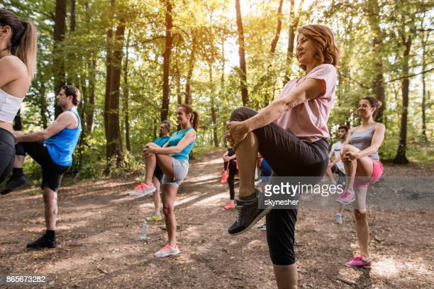 group of athletic people warming up on sports training in nature. - knees together stock photos and pictures