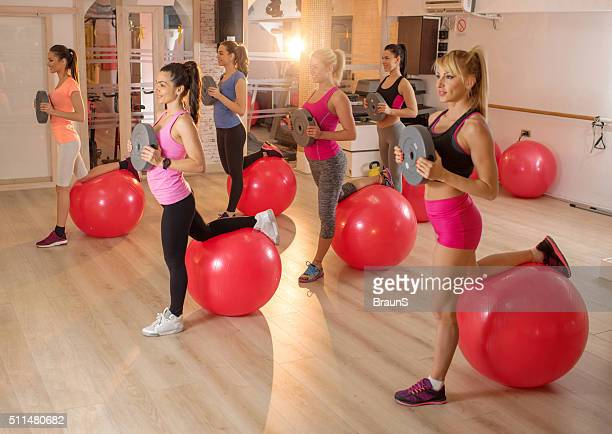 Group of athletic women exercising on aerobics class.