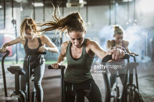 group of athletic women on exercise bikes in a health club. - ginásio imagens e fotografias de stock