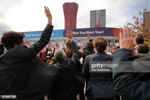 A group of attendees gather to pose for a photo outside the venue of the Mobile World Congress on the last day of the world's biggest mobile fair on...